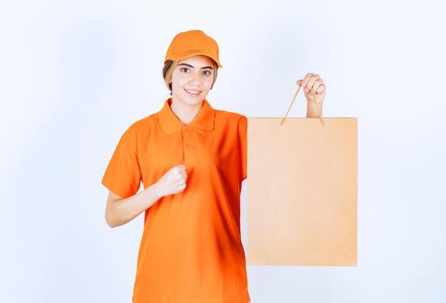 Vrouwelijke koerier in oranje uniform die een kartonnen boodschappentas levert en een teken van plezier toont