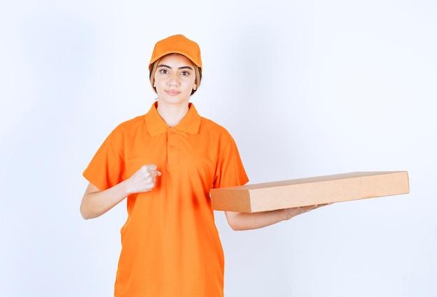 Vrouwelijke koerier in oranje uniform die een kartonnen doos aflevert en een tevredenheidshandteken toont