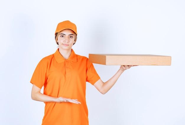 Vrouwelijke koerier in oranje uniform die een kartonnen doos aflevert