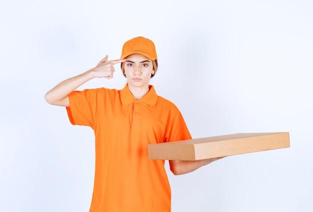 Vrouwelijke koerier in oranje uniform die een kartonnen doos bezorgt en er verward en aarzelend uitziet
