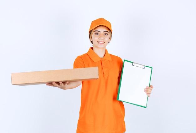 Vrouwelijke koerier in oranje uniform die een kartonnen doos vasthoudt en de handtekeninglijst presenteert