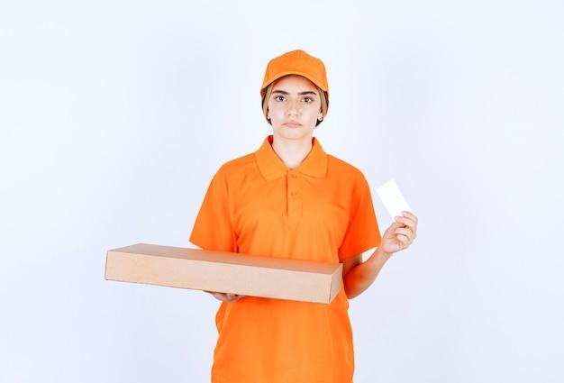 Vrouwelijke koerier in oranje uniform die een kartonnen doos vasthoudt en haar visitekaartje presenteert