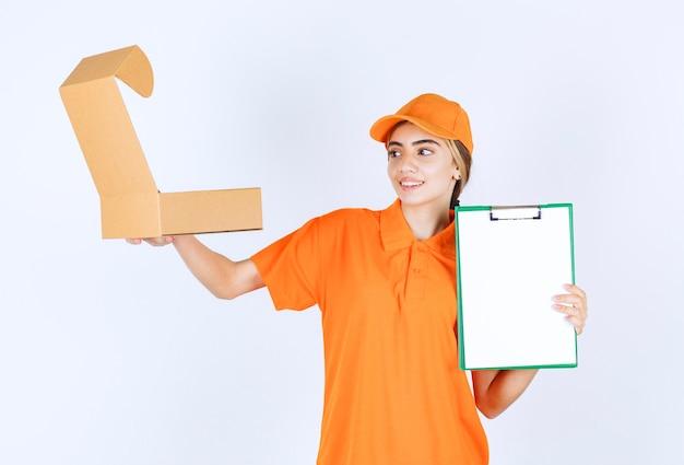 Vrouwelijke koerier in oranje uniform die een open kartonnen doos vasthoudt en de klantenlijst presenteert