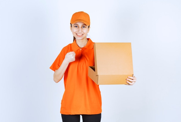 Vrouwelijke koerier in oranje uniform die een open kartonnen doos vasthoudt en haar vuist laat zien.