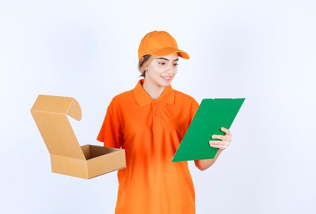Vrouwelijke koerier in oranje uniform die een open kartonnen doos vasthoudt en het groene bestand controleert