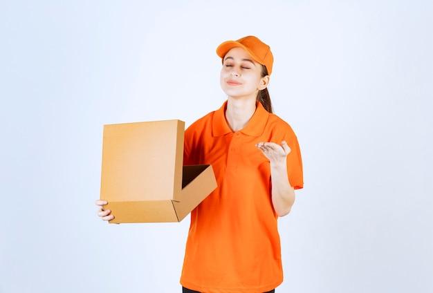Vrouwelijke koerier in oranje uniform die een open kartonnen doos vasthoudt en het product erin ruikt.