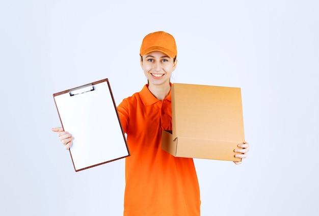 Vrouwelijke koerier in oranje uniform die een open kartonnen doos vasthoudt en om een handtekening vraagt