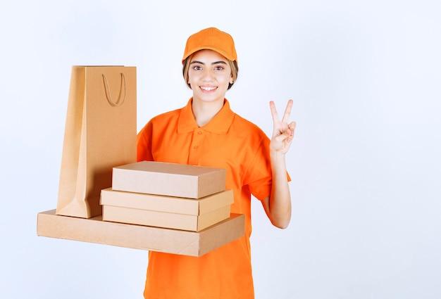 Vrouwelijke koerier in oranje uniform die een voorraad kartonnen pakjes en boodschappentassen vasthoudt en een positief handteken toont