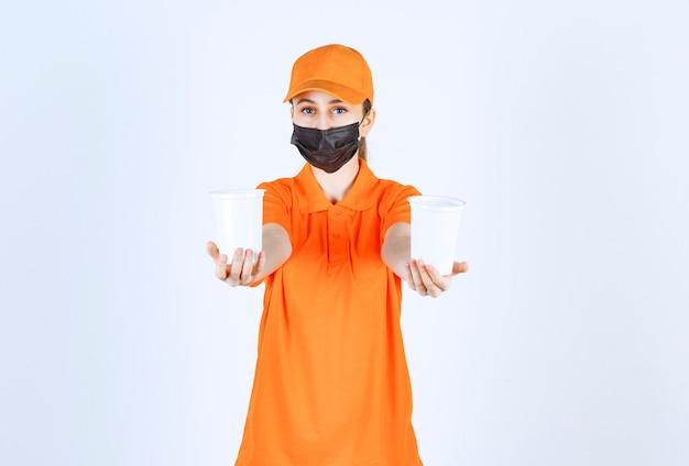 Vrouwelijke koerier in oranje uniform en zwart masker die afhaalmaaltijden in plastic bekers in beide handen houdt en aan de klant aanbiedt