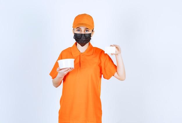 Vrouwelijke koerier in oranje uniform en zwart masker die een plastic beker vasthoudt en haar visitekaartje presenteert