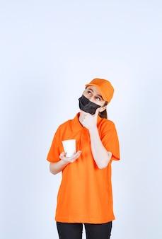 Vrouwelijke koerier in oranje uniform en zwart masker met een afhaaldrankje en denkend