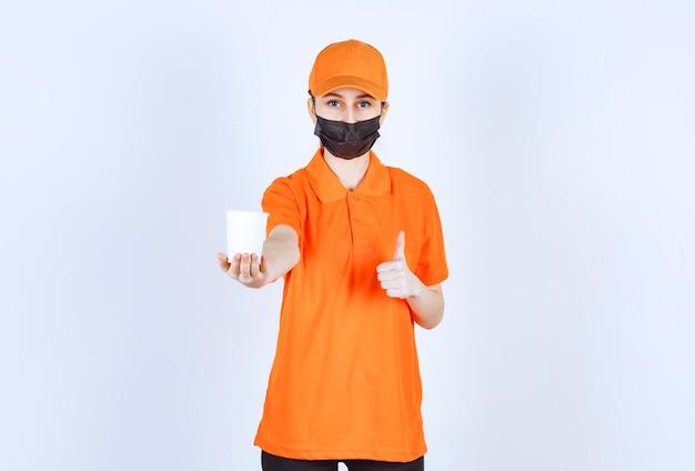 Vrouwelijke koerier in oranje uniform en zwart masker met een afhaaldrankje en genietend van de smaak