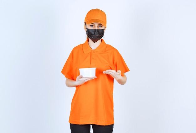 Vrouwelijke koerier in oranje uniform en zwart masker met een plastic beker en wijzend naar iets