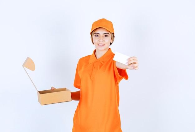 Vrouwelijke koerier in oranje uniform houdt een open kartonnen doos vast en stelt haar visitekaartje in op de klant