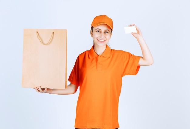 Vrouwelijke koerier in oranje uniform levert een boodschappentas en presenteert haar visitekaartje