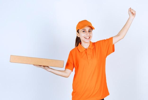 Vrouwelijke koerier in oranje uniform met een afhaalpizzadoos en toont haar vuist