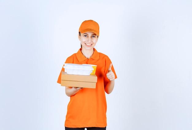 Vrouwelijke koerier in oranje uniform met een kartonnen doos, een plastic afhaaldoos en een gele noedelbeker terwijl ze een positief handteken toont