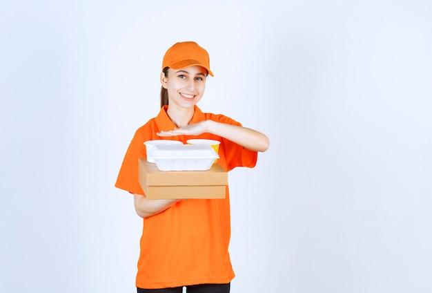 Vrouwelijke koerier in oranje uniform met een kartonnen doos, een plastic afhaaldoos en een gele noedelbeker