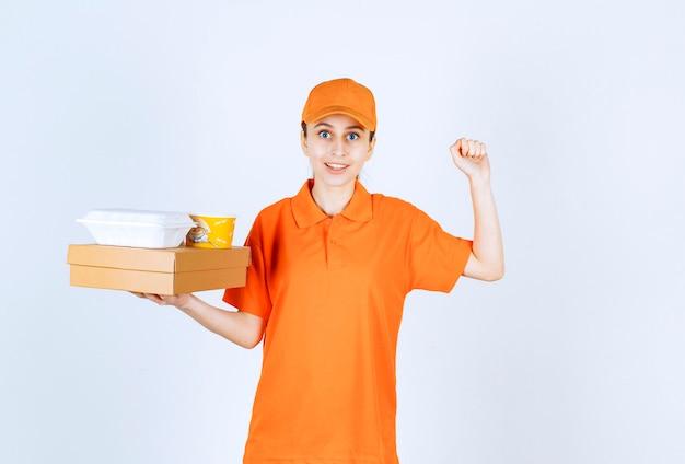 Vrouwelijke koerier in oranje uniform met een kartonnen doos, een plastic afhaaldoos en een gele noedelsbeker terwijl ze een positief handteken toont.