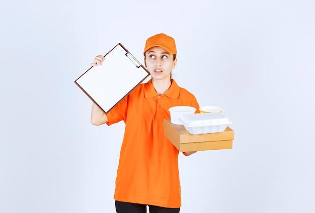Vrouwelijke koerier in oranje uniform met een kartonnen doos en een plastic afhaaldoos erop en vraagt om een handtekening.
