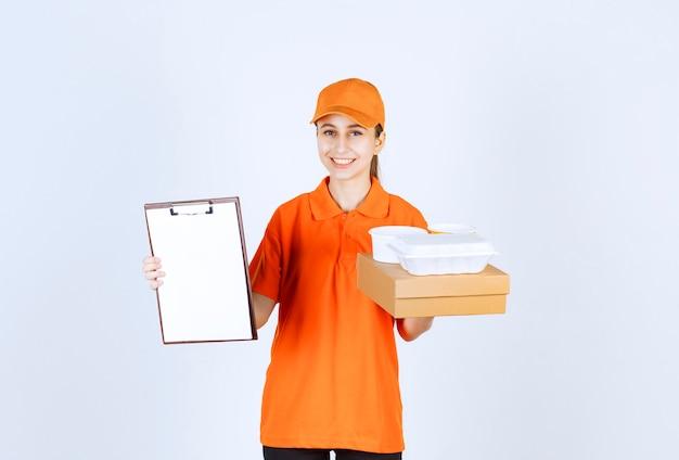 Vrouwelijke koerier in oranje uniform met een kartonnen doos en een plastic afhaaldoos erop en vraagt om een handtekening