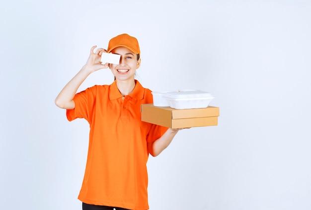 Vrouwelijke koerier in oranje uniform met een kartonnen doos en een plastic afhaaldoos erop terwijl ze haar visitekaartje presenteert.