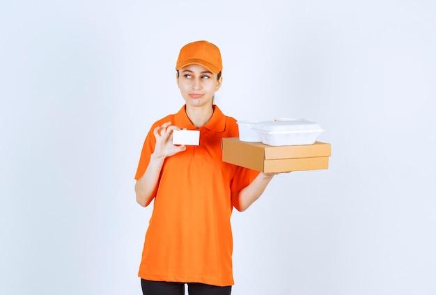 Vrouwelijke koerier in oranje uniform met een kartonnen doos en een plastic afhaaldoos erop terwijl ze haar visitekaartje presenteert