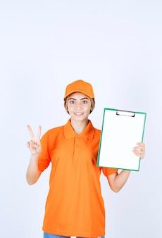 Vrouwelijke koerier in oranje uniform met een klantenlijst en een teken van tevredenheid