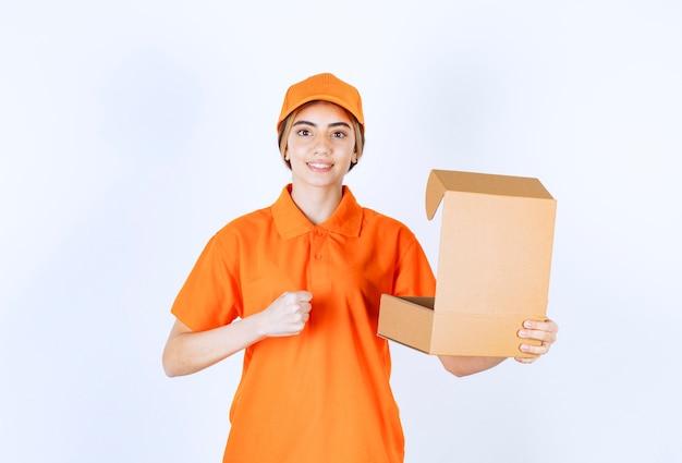 Vrouwelijke koerier in oranje uniform met een open kartonnen doos en een teken van plezier
