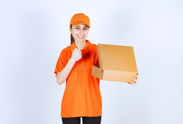 Vrouwelijke koerier in oranje uniform met een open kartonnen doos en toont haar vuist