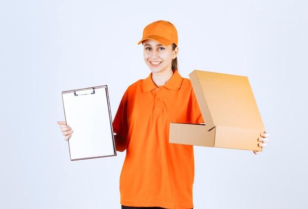 Vrouwelijke koerier in oranje uniform met een open kartonnen doos en vraagt om een handtekening.