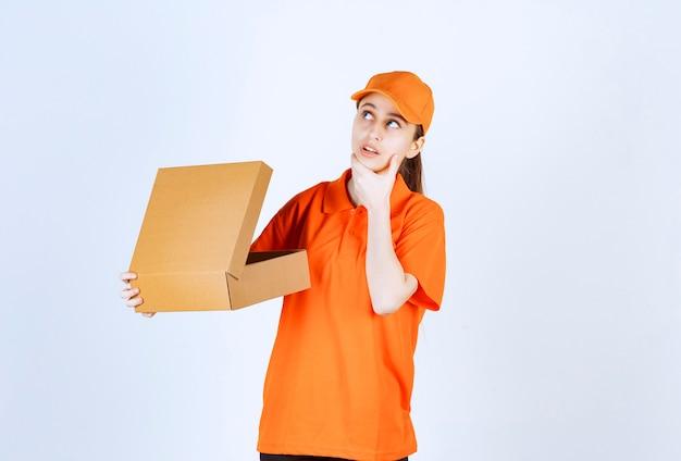Vrouwelijke koerier in oranje uniform met een open kartonnen doos en ziet er verward en attent uit