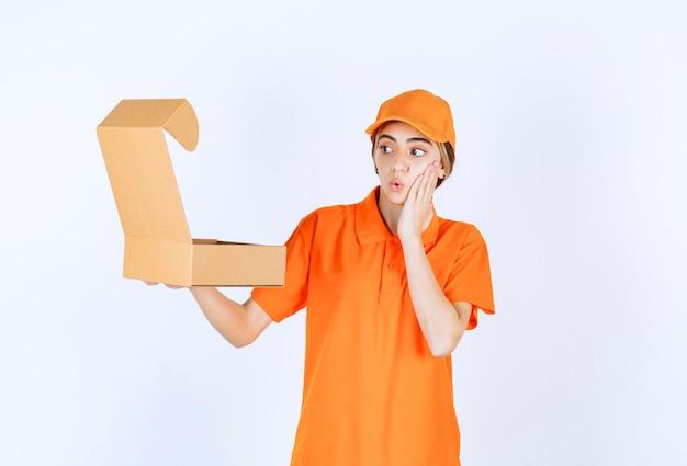Vrouwelijke koerier in oranje uniform met een open kartonnen doos en ziet er verward uit