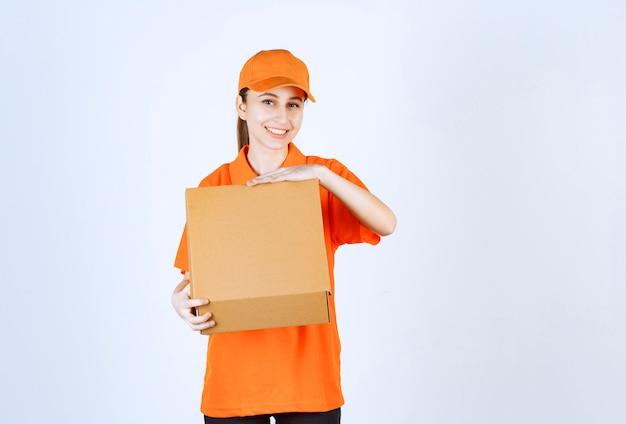 Vrouwelijke koerier in oranje uniform met een open kartonnen doos