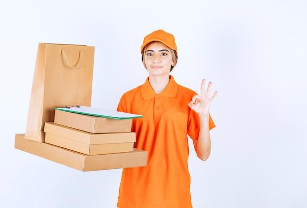 Vrouwelijke koerier in oranje uniform met een voorraad kartonnen pakjes en boodschappentassen en geniet van de kwaliteit van de dienstverlening