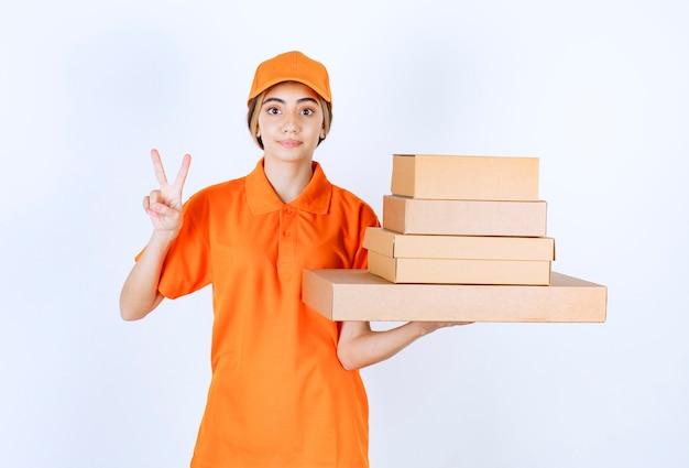 Vrouwelijke koerier in oranje uniform met een voorraad kartonnen pakjes en ziet er positief uit