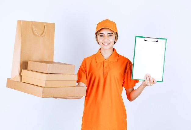 Vrouwelijke koerier in oranje uniform met een voorraad kartonnen pakketten en boodschappentassen en presenteert de handtekeninglijst aan de klant
