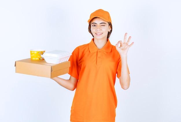 Vrouwelijke koerier in oranje uniform met gele en witte afhaaldozen met een kartonnen pakket en genietend van de smaak