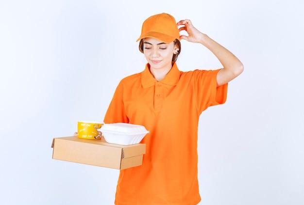 Vrouwelijke koerier in oranje uniform met gele en witte afhaaldozen met een kartonnen pakket en ziet er verward en attent uit