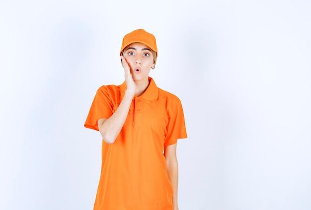 Vrouwelijke koerier in oranje uniform ziet er doodsbang en bang uit