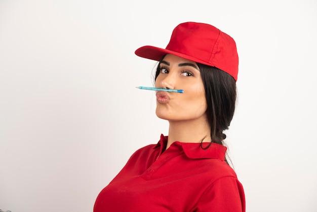 Vrouwelijke koerier in rode uniforme pen op haar mond te houden. hoge kwaliteit foto