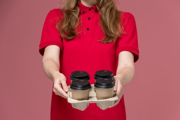 Vrouwelijke koerier in rood uniform bedrijf bezorging koffiekopjes bezorgt ze op roze, baan uniforme werknemer dienstverlening