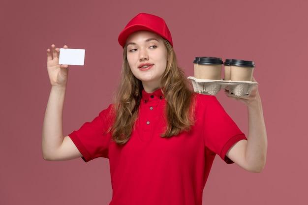 Vrouwelijke koerier in rood uniform bedrijf levering koffiekopjes en kaart op lichtroze, baan uniforme service werknemer levering