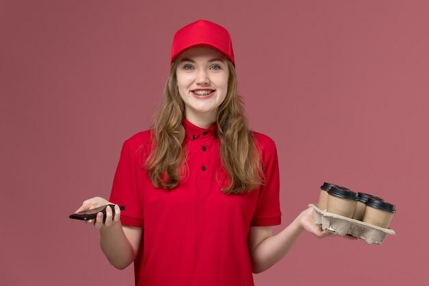 Vrouwelijke koerier in rood uniform bedrijf levering koffiekopjes en telefoon lachend op roze, uniforme baan werknemer dienstverlening