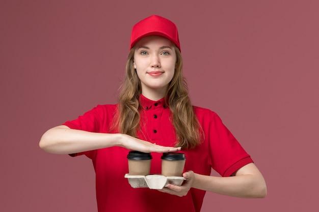 Vrouwelijke koerier in rood uniform bedrijf levering koffiekopjes met een lichte glimlach op lichtroze, baan uniforme service werknemer levering
