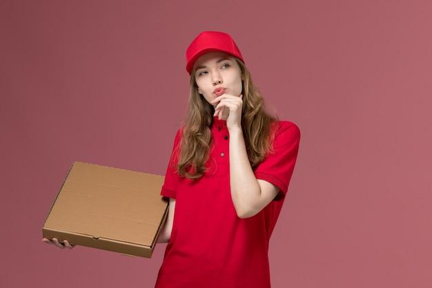 Vrouwelijke koerier in rood uniform denken voedseldoos op roze, uniforme dienstverlening te houden baan
