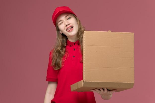 Vrouwelijke koerier in rood uniform die bruine levering houdt en voedseldoos op lichtroze, uniforme baandienstmedewerker opent
