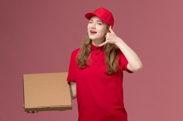 Vrouwelijke koerier in rood uniform die de doos van de voedsellevering op roze, uniforme baan van de dienstverlener houdt