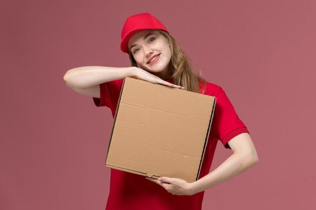 Vrouwelijke koerier in rood uniform die de doos van de voedsellevering op roze, uniforme dienstlevering baan houdt