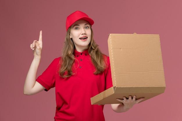 Vrouwelijke koerier in rood uniform die voedseldoos houdt die het opent op lichtroze, baanuniforme servicemedewerker